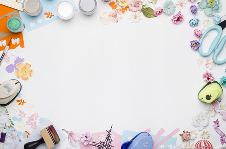 Empty white space in the center surrounded by paper flowers, multi-colored paper and scrapbooking materials. Top view Banque d'images - 104966576