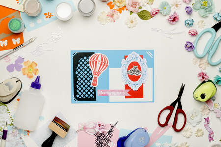 Bright card in the center on a white background surrounded by colorful paper, paper flowers and scrapbooking materials. Top view Banque d'images - 104966582