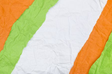 Background of strips of crumpled paper orange green and white