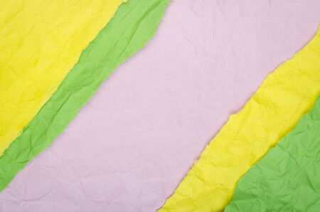Background of yellow, green and pink crumpled paper