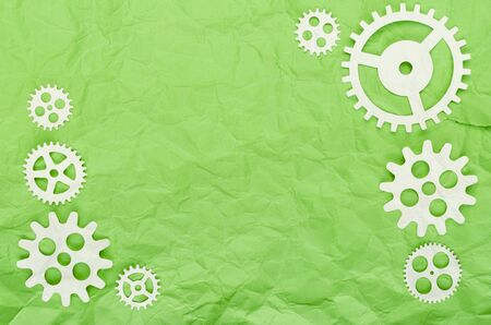 Background of green crumpled paper and white paper gears abstract