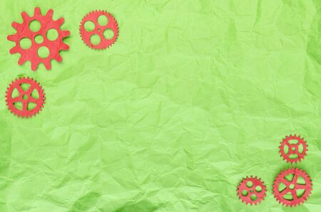 Background of green crumpled paper and red paper gears abstract