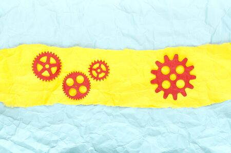 Background crumpled paper with yellow stripe and red paper gears