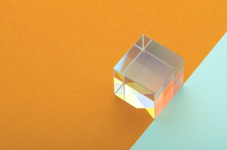 iridescent glass square prism on orange blue background Banque d'images