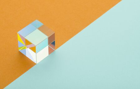 colorful iridescent square prism on orange blue background, minimalism, abstraction
