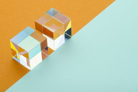 two iridescent glass cubes on an orange and blue background Banque d'images