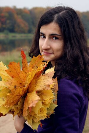 A girl standing in the autumn forest smiling with a bouquet   photo