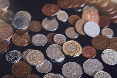 Top view New one pound sterling coin and penny on black background, Pile of different British money coins for business exchange, financial business investment and econom concept Archivio Fotografico