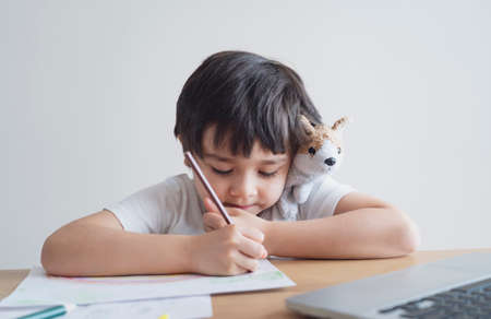 Kid in self isolation siting with notebook on table doing homework,Happy Child boy writing or drawing on white paper, Elementary school and home schooling, Distance Education,E-learning online concept