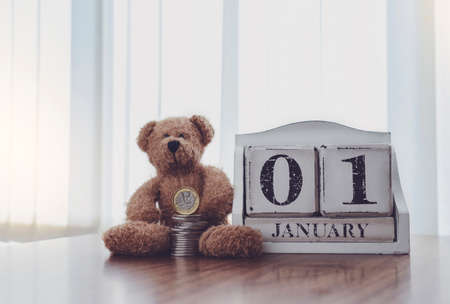 First of January with teddy bear and stack pound coin,Financial planing for New Yew 2021,New Year resolution for saving money for the future in business or personal life concept for holiday background 版權商用圖片