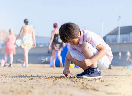 Portrait of lonly little boy playing alone on beach, Kid using shell writing  on the sand. Child playing on the beach during summer time.