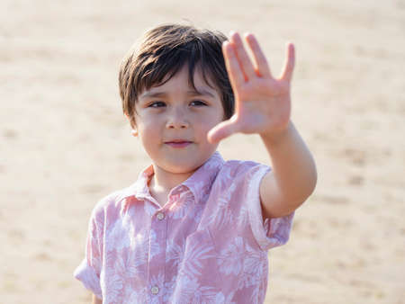 Selective focus of  little boy showing five fingers, Portrait kid primary school counting number five, Child showing five numbers with fingers, Education or Toddler development concept