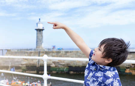 Portrait of cute little boy pointing finger up to sky, Side view active Kid looking up with curious face, Young boy traveler standing on the bridge with blurry lighthouse at Whitby harbor background.