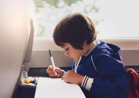 Selective focus of little boy draws with coloured pen on white paper, Kid traveling by the train, Little boy in a high speed express train on family vacation, Entertainment for young passenger.