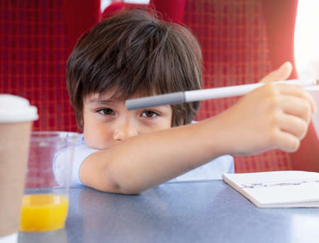 Portrait kid looking at camera with hand holding colour pen, Child with bored face sitting on the train, Cute young boy sitting next to window  traveling by train on summer day, Kid and family vacation concept Banque d'images