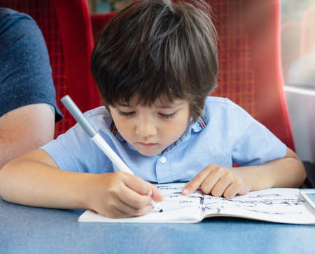 Kid traveling by the train, Child drawing or watching cartoon on teplet sitting by the window. Little boy in a high speed express train on family vacation, Entertainment for young passenge Banque d'images