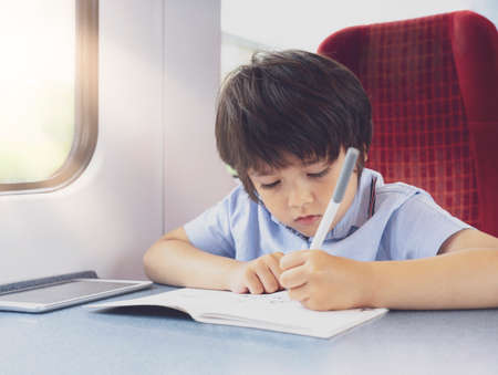 Kid traveling by the train, Child drawing or watching cartoon on teplet sitting by the window. Little boy in a high speed express train on family vacation, Entertainment for young passenger. Banque d'images