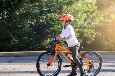 School kid learns to ride a bike in the Park, Portrait of a cute little boy on bicycle,  Child in helmet riding a cycling on the road. Фото со стока