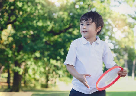 Portrait of school boy have fun with flying disc in the park, Sport and recreation  for children concept