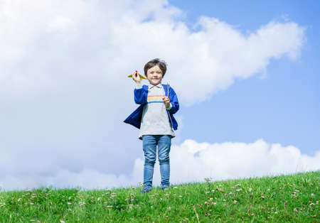 Portrait active little boy playing with toy airplane against green nature background, Child throwing foam airplane, Kid playing in the park,  Childhood outdoor activity concept. Фото со стока - 150296129