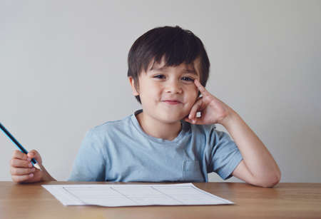 Portrait of preschool kid boy making homework at home. Happy Child holding pencils and looking at camera with smiling face, Little boy is writing at the table, Elementary school and education concept Фото со стока