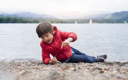 Happy kid playing pebbles and leaves with blurry nature background, Chid lyingdown on pebbles by the lake playing alone in sunny day, little boy playing outdoor in spring or summer