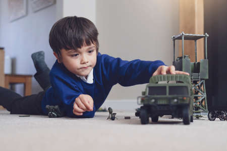 Portrait of School boy lying down on the carpet floor playing with soldiers, military car and figurine toys, Happy Kid playing wars and peace on his own at home, Children imagination and development