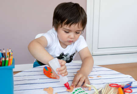 little boy making Easter greeting card,Materials for art creativity on kid table, 3 years old boy gluing on color paper, Crafts activity in kindergarten with parents, Home schooling concept Фото со стока