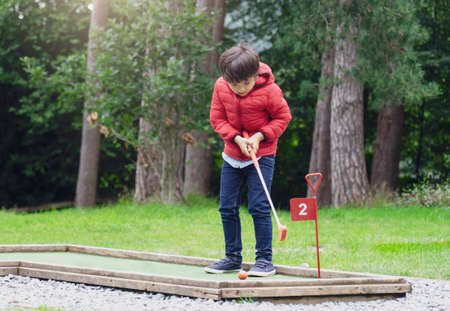 Portrait of Happy child playing mini golf in the park, Active Kid boy playing crazy golf on holiday, Children enjoying his vacation outdoors activity
