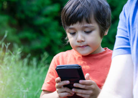 Cropped shot Kid boy siting in the park with parent playing game on smart phone,  Child looking at mobile phone with blurry green nature background. happy family concept Фото со стока