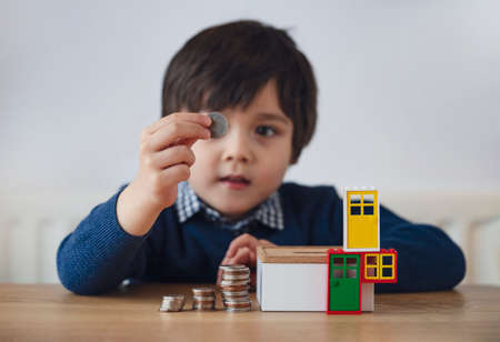 Blurry face of preschool kid showing 10 pence with smiling face, Selective focus kid boy  making stack money coins and counting before puting in money box. Learning financial responsibility and planning Zdjęcie Seryjne
