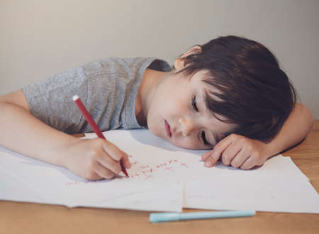 Emotional portrait of lonely child writing a messages to his mother, Preschool kid using red colour writing and drawing on white paper, Little boy with sad lying head down on table.