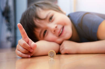 Blurry image of Kid face laying dow on wooden floor showing money coin, Selective focus of happy child pointing finger up and playing with one pound coin. Positive children concept