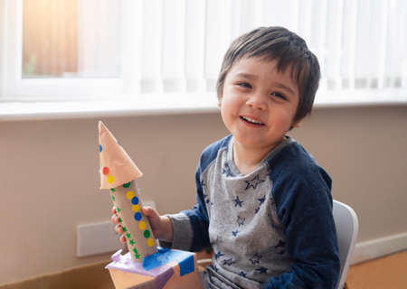 Cute little boy playing with spaceship, Happy child holding toy rocket, Portrait of funny kid, Toddler creativity, Concept for diy, art and craft in a classroom or Learning and education concept