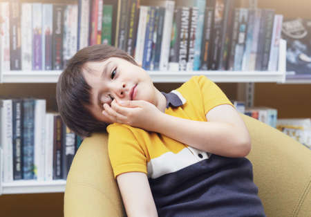 Tired little boy rubbing his eyes while sitting in school library, lazy stressed child fall asleep and bored with reading a book. Banque d'images