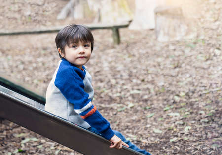 Happy kid sitting on slide in forest Autumn park, Active child wearing jumper playing outdoor in playground, Portrair little boy looking at camera with smiling face