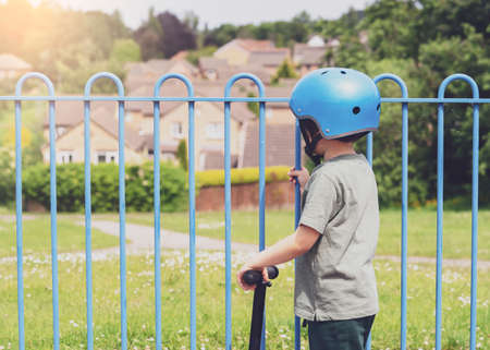 Rear view portrait ofSad little boy looking through metal fence , Lonely kid playing scooter alone in playground, Portrait Child in safety helmet riding a roller in the park on sunny summer.  Stock Photo