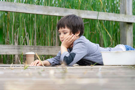 Outdoor portrait of happy boy lying on wooden bridge reading some thing on paper,Active child having fun playing in wildlife park,Kid having adventure in nature reserve in sunny day summer Archivio Fotografico - 150297273