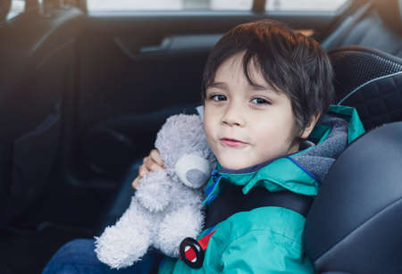 School kid taking his teddy bear traveling with him for explorer on his vocation, Child boy sitting in car seat with belt on shoulder and holding his soft toy looking out of the car