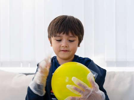 Selective focus of kid wearing disposable protective plastic glove and holding yellow balloon,Kid preparing science project about static charged, Child looking curiously at science experiment,Home schooling concept