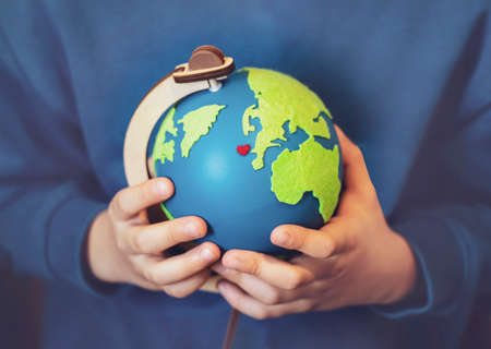 Cropped shot little boy holding the earth in his hands. Hands holding globe with red heart on map, Earth day on April 22 , Green World environment day concept Reklamní fotografie