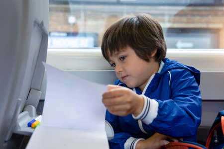 Kisd open a book and reading while traveling to school by the train, Child sitting next to window of a high speed train, Entertainment or activity for little traveler or young passenger