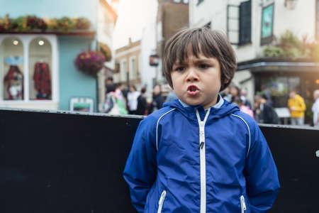 Outdoor portrait of young boy standing alone on street with with blurry background of people, Dramatic portrait of Kid with angry face .Spoiled children concept