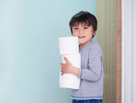 Side view portrait of cute kid holding toilet roll standing in the front of toilet, Child boy looking at camera with smiling face while carrying a stack of toilet paper