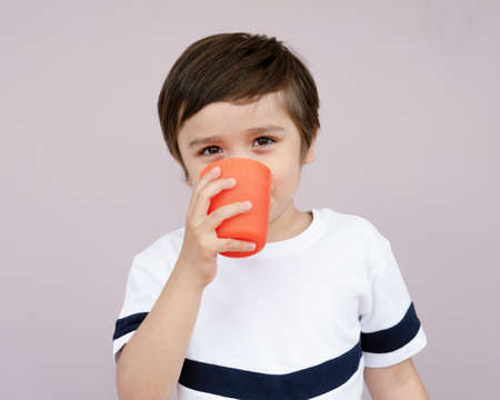 Isolated cute boy drinking orange juice from plastic glass on light purple background, Healthy 4-5 year old boy drinking glass of mixed fruits juice or water. Helathy life style concept