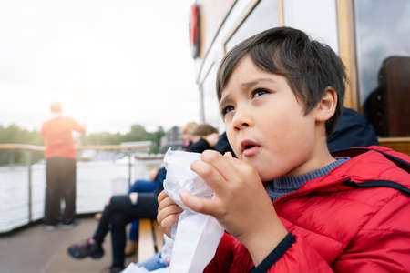 Low view portrait hungry kid eating snack while sitting in boat, cute little boy with dirty face of croissant looking up to sky, Young traveler exploring and learning about the world concept