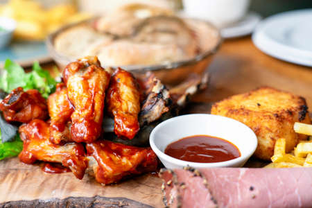 Selective focus of mixed meats, Grilled ribs, chicken wings with French fries on wooden plate, Top view Mixed bbq meat platter. Archivio Fotografico