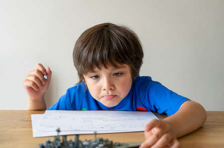 Portrait kid drawing battleship, Child boy playing with model ship toy and sketching on paper, Indoors activity concept, Home schooling, Distance education