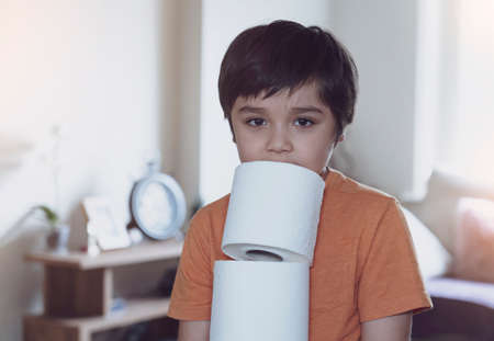 Child carrying a stack of toilet paper with blurry living room background, kid holding toilet roll, Young boy suffers from diarrhoea holding toilet paper,  Children health care