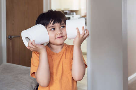 Happy young boy with smiling face playing with toilet paper, kid putting  toilet roll on his ears, Child holding two white tissue, Children health care concept 版權商用圖片 - 151323991